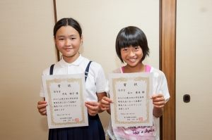 Rinko and Aika proudly show their English recitation awards.